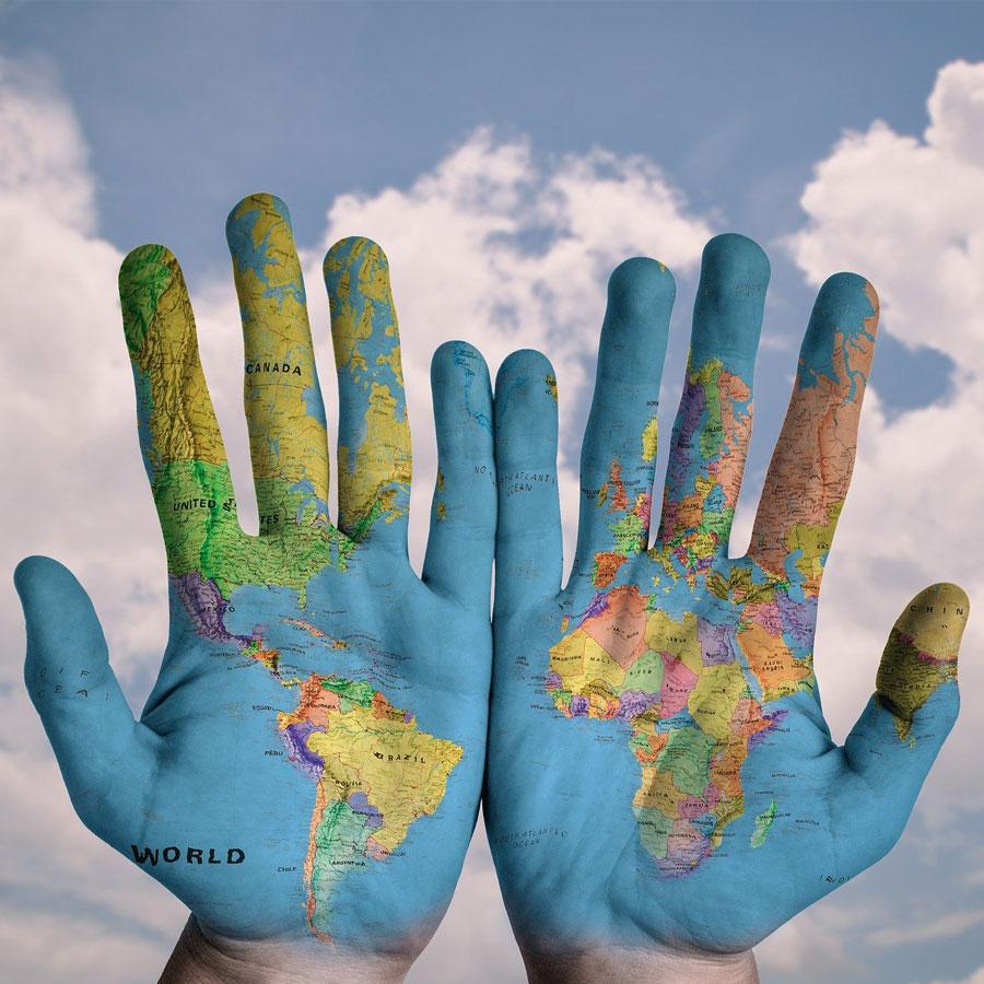 Kaksi kättä, johon on maalattu maailman kartta.