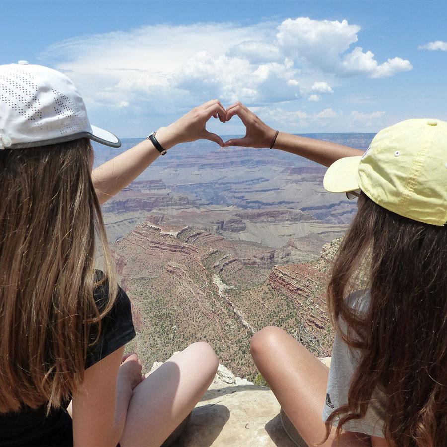Kaksi tyttöä istuvat korkean vuoren huipulla ja yhdistävät kätensä sydämen muotoiseksi.