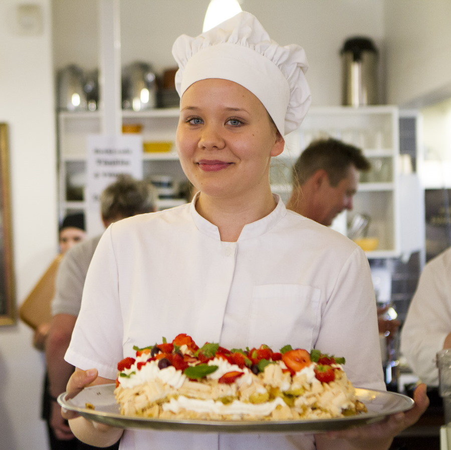 Hymyilevä kondiittori tuo tarjolle kakkua, jossa mansikoita, marenkia ja kermavaahtoa.