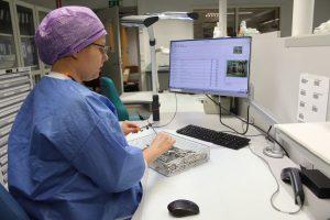 Sairaalan suojavaatteisiin pukeutunut nainenainen työskentelee tietokoneen ääressä.