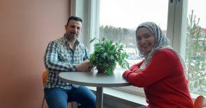 Maahanmuuttajamies ja maahanmuuttajanainen istuvat ikkunan ääressä ja hymyilevät