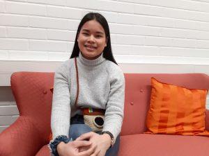Nuori hymyilevä nainen istuu sohvalla