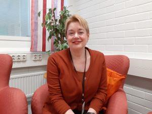 Hymyilevä nainen istuu sohvalla.