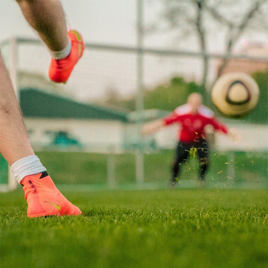 Jalkapalloilija potkaisee pallon kohti maalia.