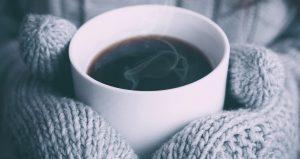 Lähikuva henkilöstä, joka pitää lapaset kädessä höyryävän kuumaa kahvikuppia.