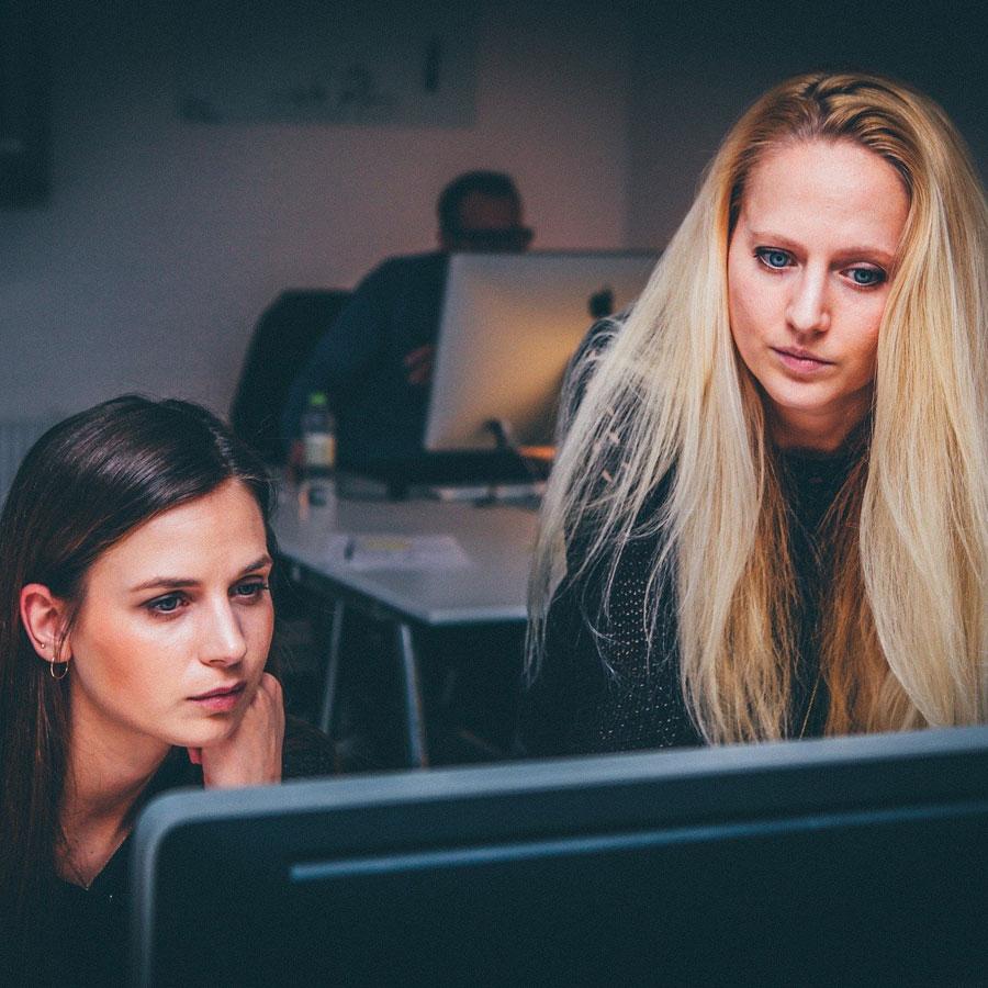 Kaksi naista työskentelevät tietokoneen ääressä.