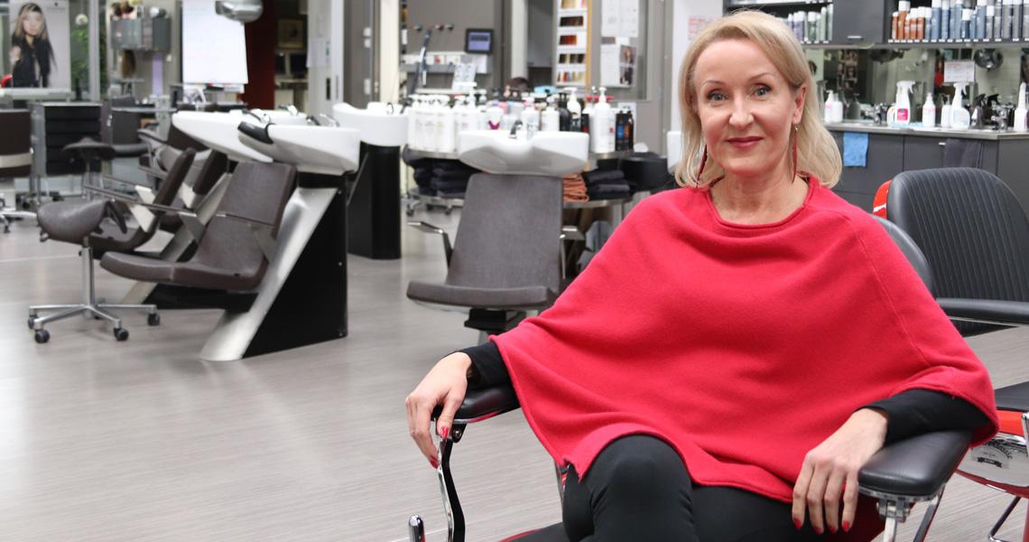 Mila istuu kampaamon tuolissa Kauneustalon opetustilassa