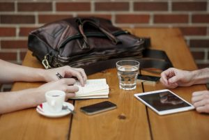 kaksi ihmistä juo pöydän ääressä kahvia.
