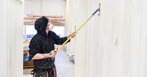 Pintakäsittelijäopiskelija pesee seinää käsittelyä varten.