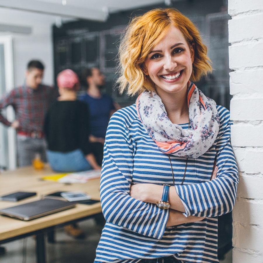 Nainen nojaa seinään työhuoneessa ja taustalla on ihmisiä juttelemassa toisilleen.