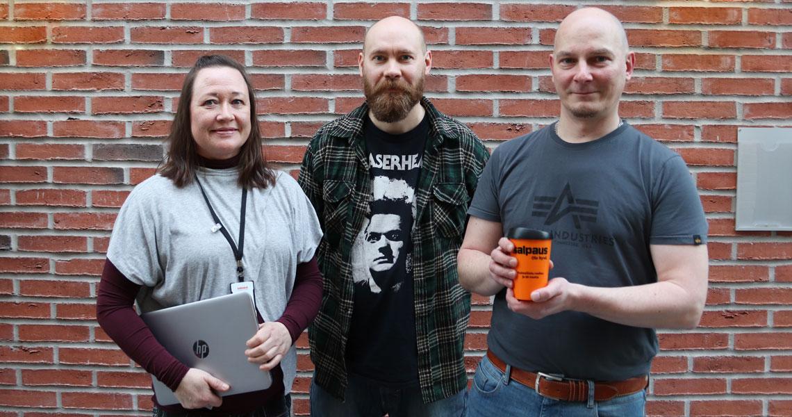 Kolme henkilöä rivissä, ensimmäisellä kädessään tietokone ja kolmannella kahvikuppi
