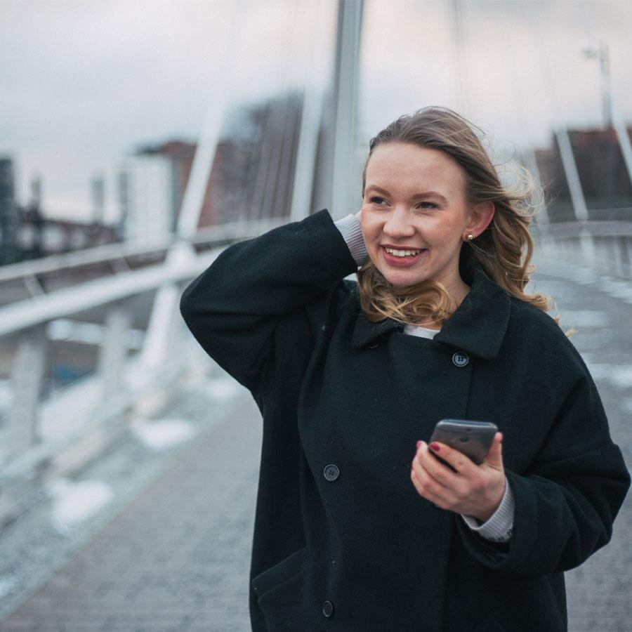 Iloinen opiskelija pitää puhelinta kädessään ja kävelee sillalla.
