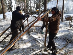 """""""Opiskelijat rakentavat laavua lumiseen metsään."""""""