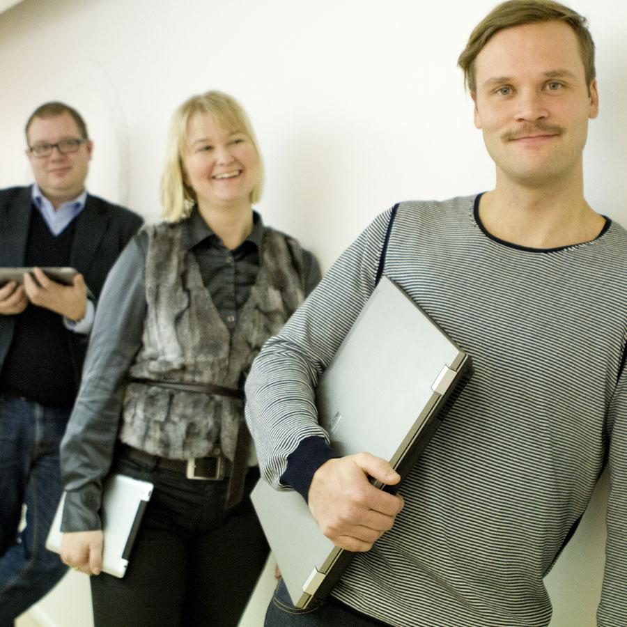 Kolme henkilöä nojaa seinään, heillä on kannettavat tietokoneet käsissään.
