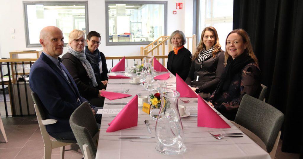 Kuusi henkilöä lounaspöydän ääressä istumassa