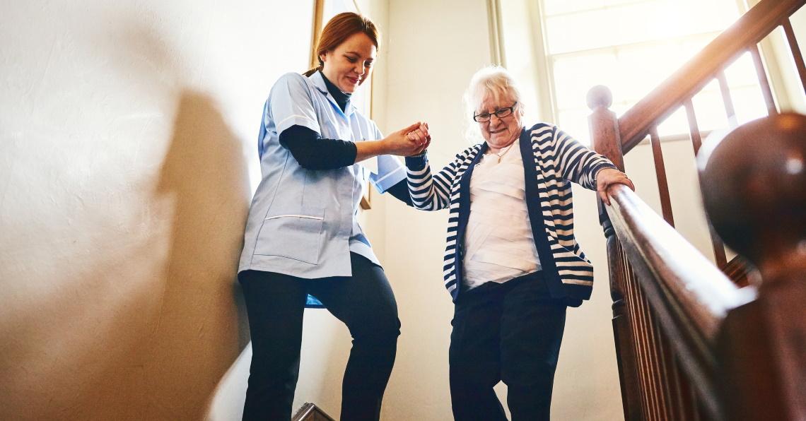 Hoitaja avustaa iäkästä naista portaissa.