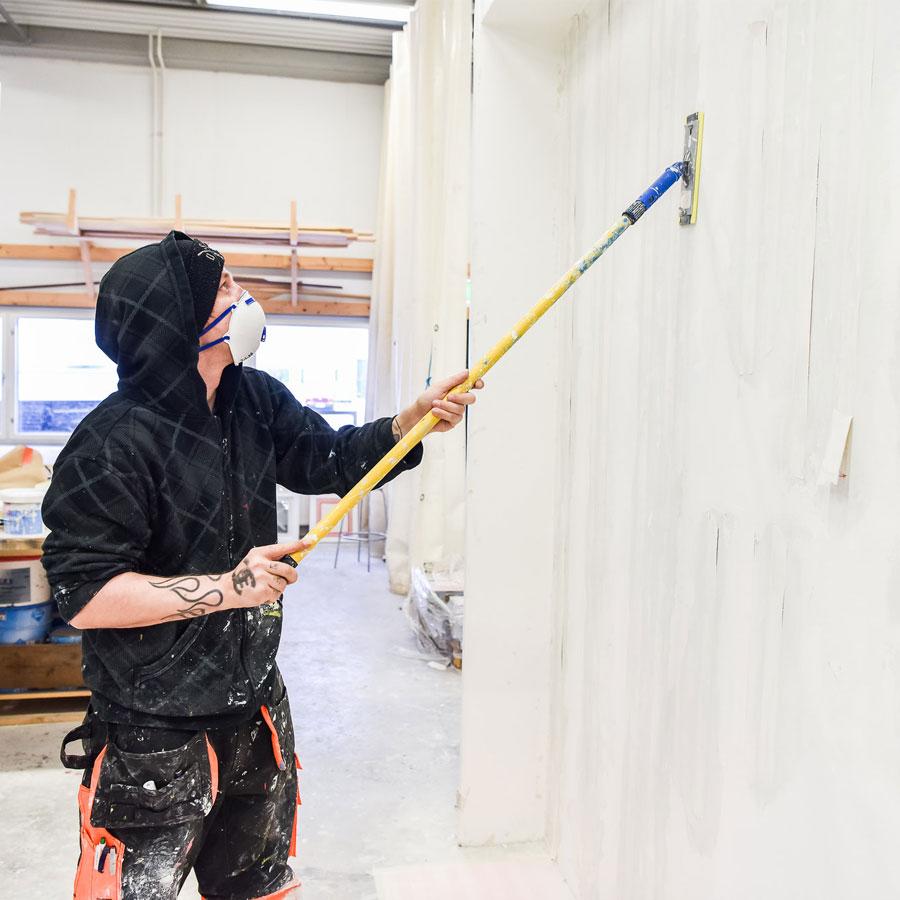 Henkilö pesee seinää ennen maalauksen aloittamista.