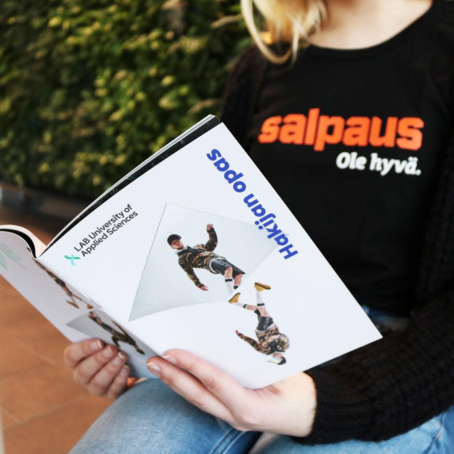 Salpaus-paitainen henkilö lukee LABin hakijan opasta