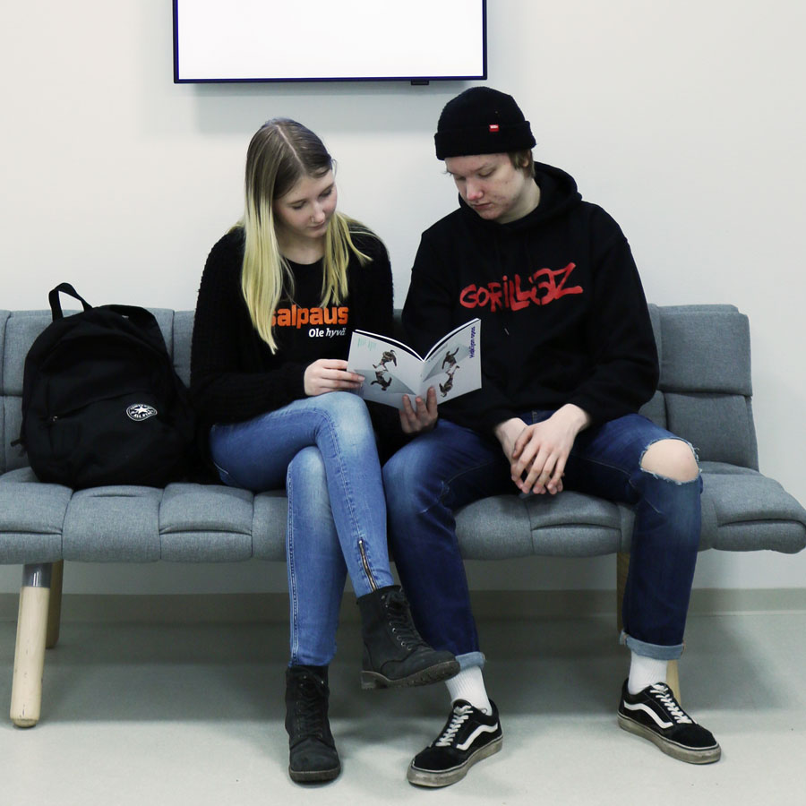Kaksi opiskelijaa tutkii sohvalla esitettä