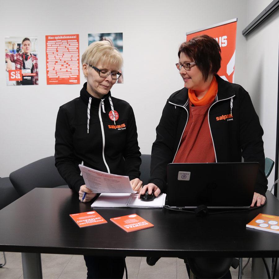 Kaksi naista pöydän ja tietokoneen ääressä, tutkailevat esitettä.
