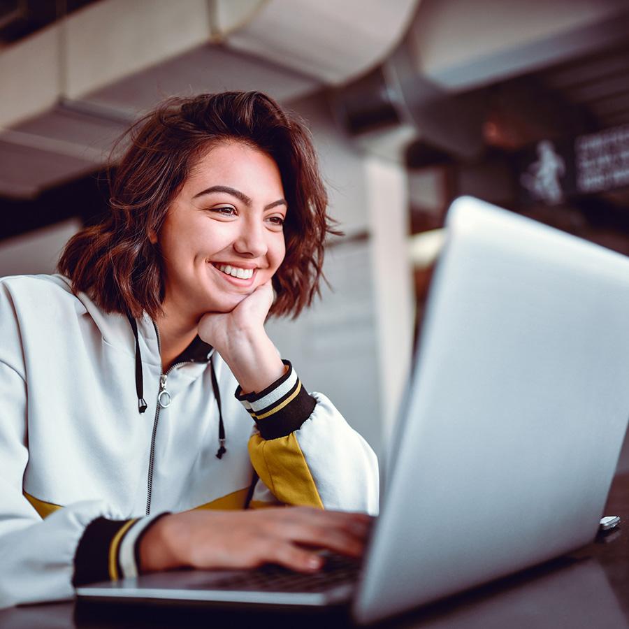 """""""Hymyilevä nainen työskentelee kannettavalla tietokoneella."""""""