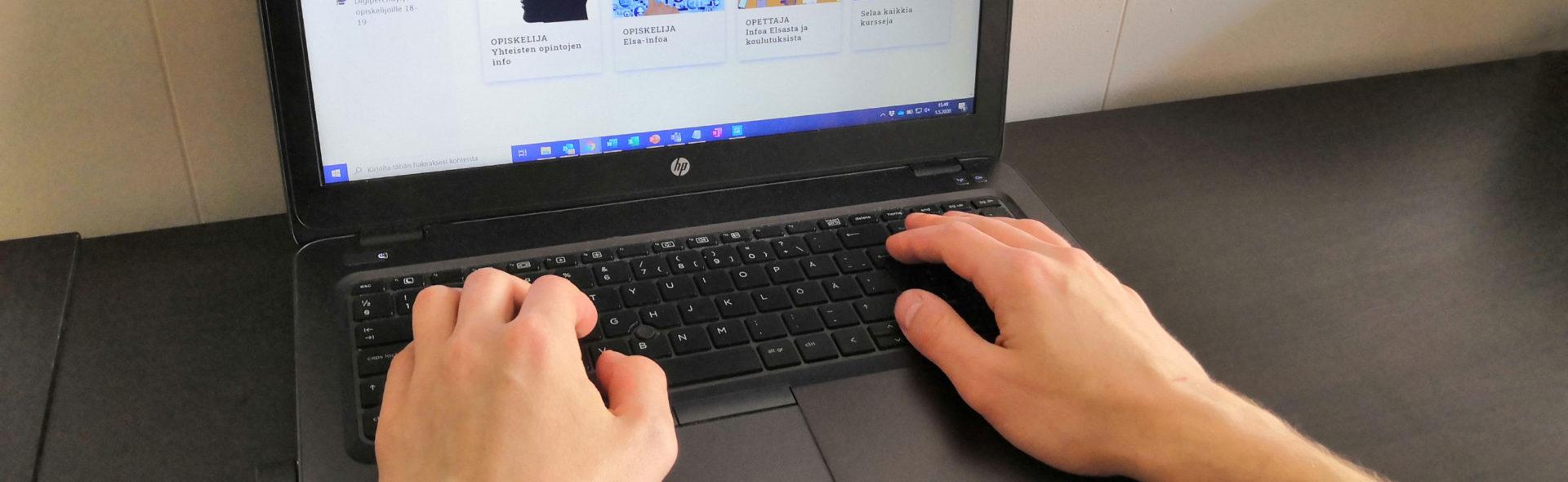 Kädet ovat tietokoneen näppäimistöllä.