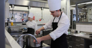 Kaksi kokkiopiskelijaa keittiössä valmistamassa ruokaa.