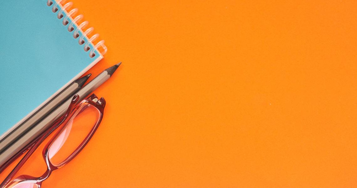 Oranssilla pöydällä on silmälasit, vihko ja kaksi kynää.