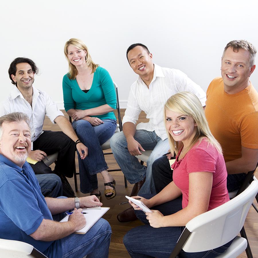 """""""ryhmä miehiä ja naisia istuu tuoleilla ringissä ja hymyilevät iloisesti"""""""