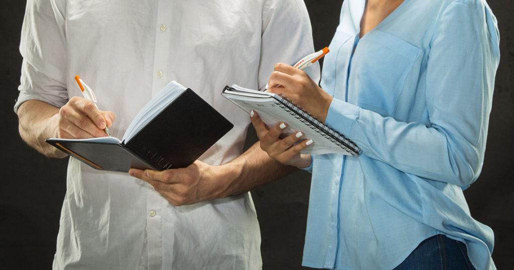 Kaksi henkilö kirjoittaa muistikirjoihin Salpauksen kynillä.