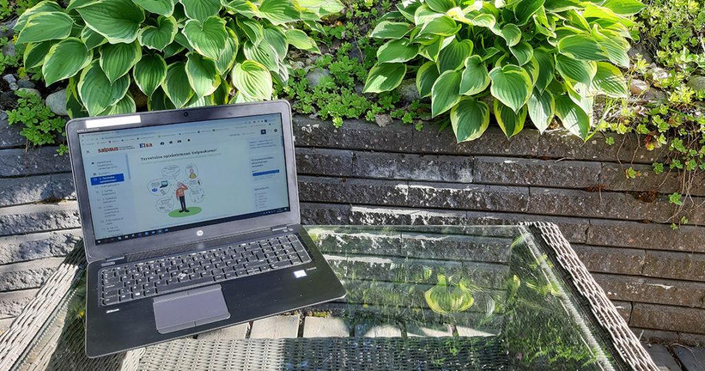 Tietokone pöydällä puutarhassa.