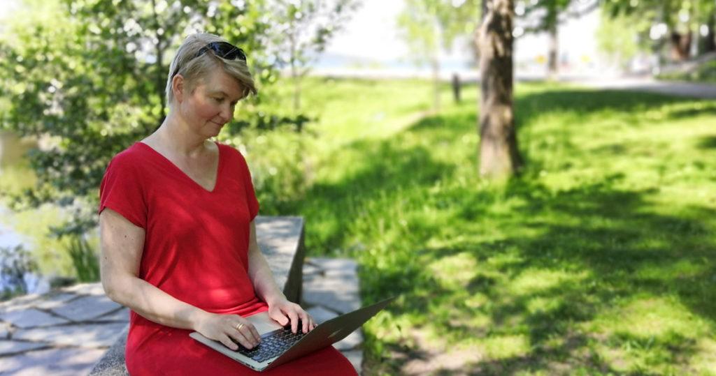 Nainen istuu puistossa tietokone sylissään.
