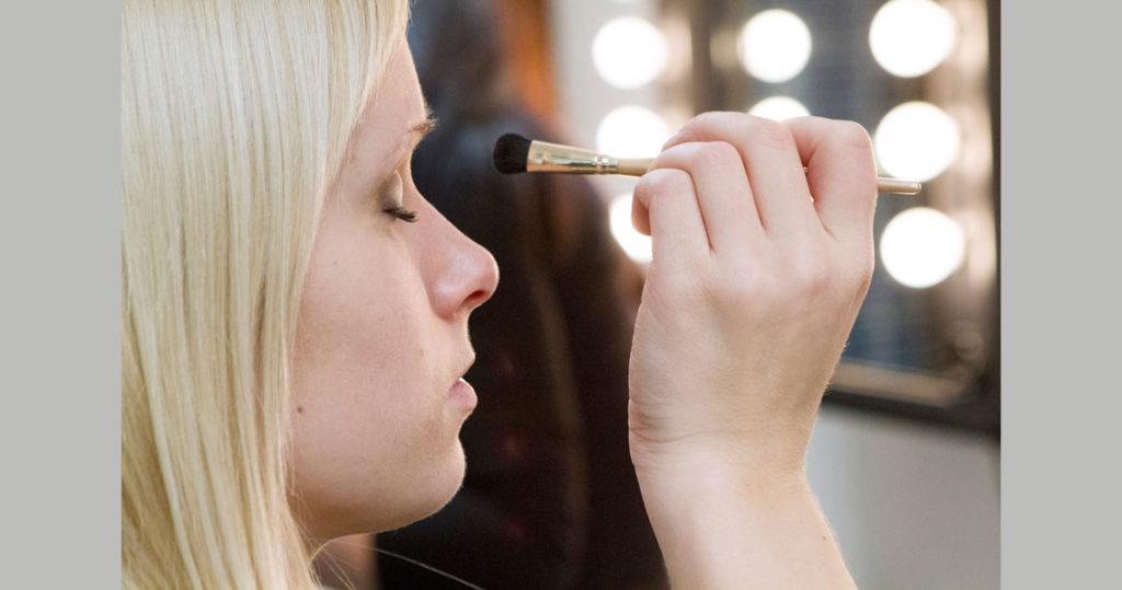 Toinen henkilö tekee tytölle silmämeikkiä.