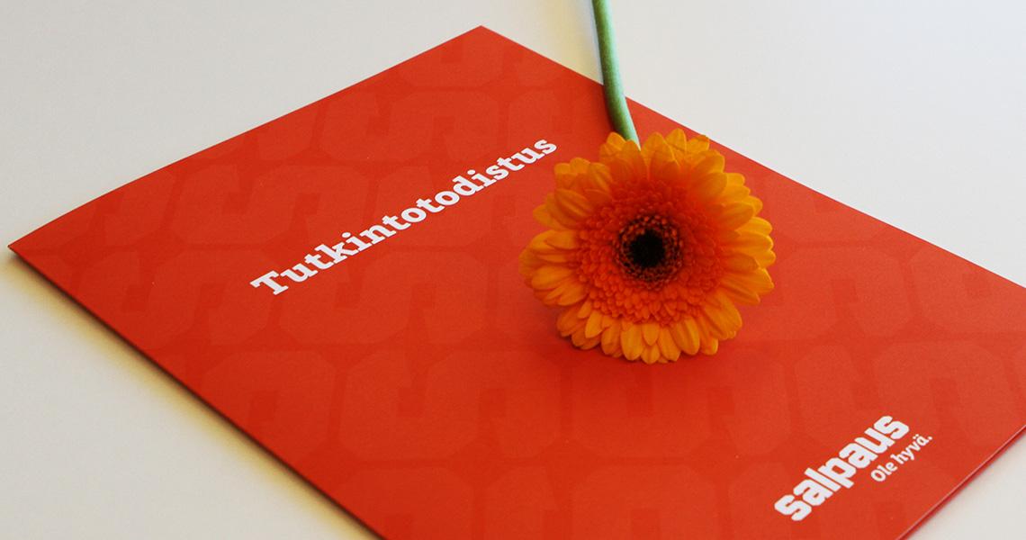 Salpauksen oranssi tutkintotodistus ja kukka.