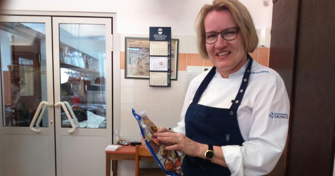 Ravintolan keittiössä nainen kokin vaatteissa pitää ruokatuotetta käsissään ja hymyilee.