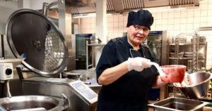 Nainen mustassa kokin asussa ottaa hilloa isolla kauhalla suurtalouskeittiössä.