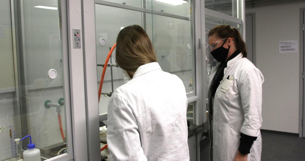 Kaksi naista laboratoriotakeissa työskentelee vetokaapin ääressä.