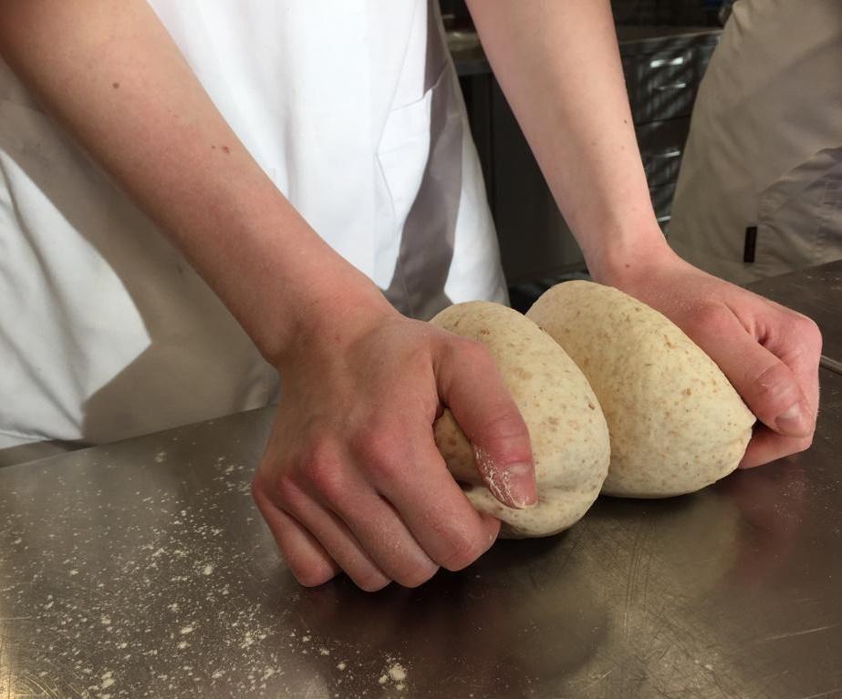 Kädet, jotka leipovat sämpylöitä.