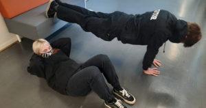 Kaksi opiskelijaa tekee liikuntasuorituksia koulun käytävällä. Toinen punnertaa ja toinen tekee vatsalihasliikkeitä.