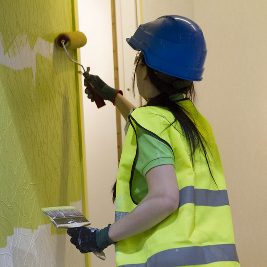Kuva, jossa henkilö maalaa seinää.