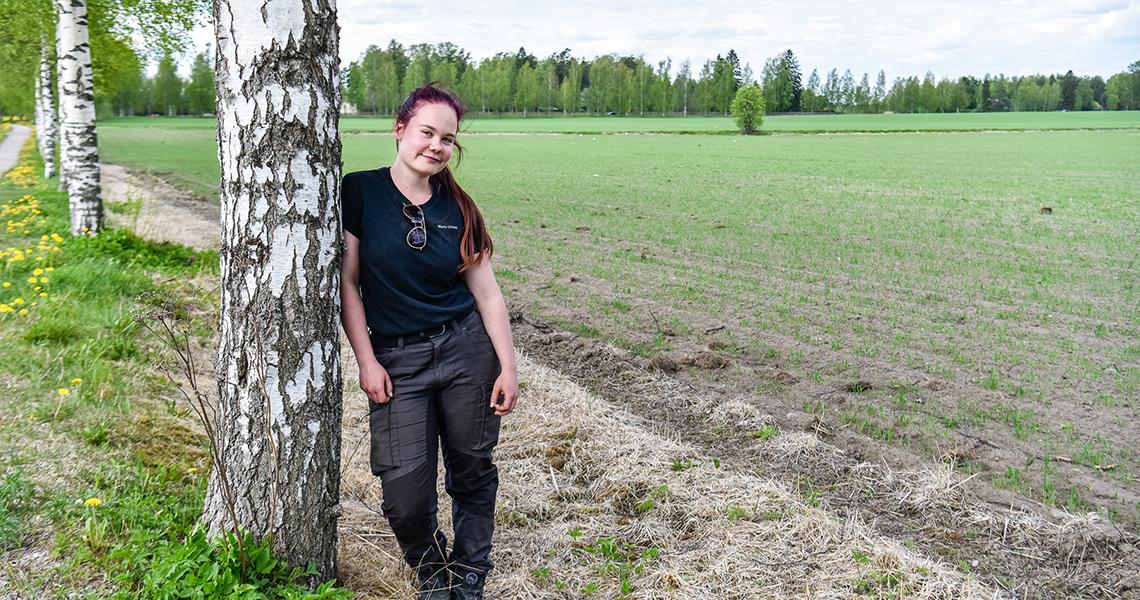 Tyttö nojaa koivuun keväällä pellonreunassa.