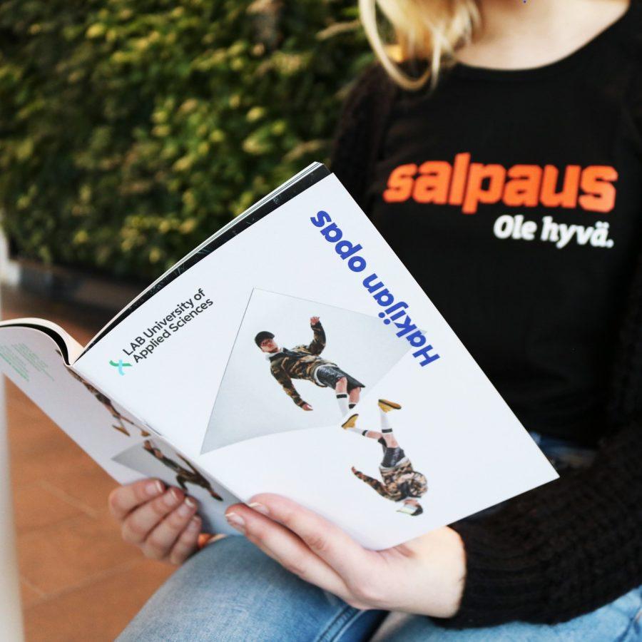 Henkilö jolla on päällä Salpaus tekstillä oleva paita lukee LAB ammattikorkeakoulun hakijan opasta