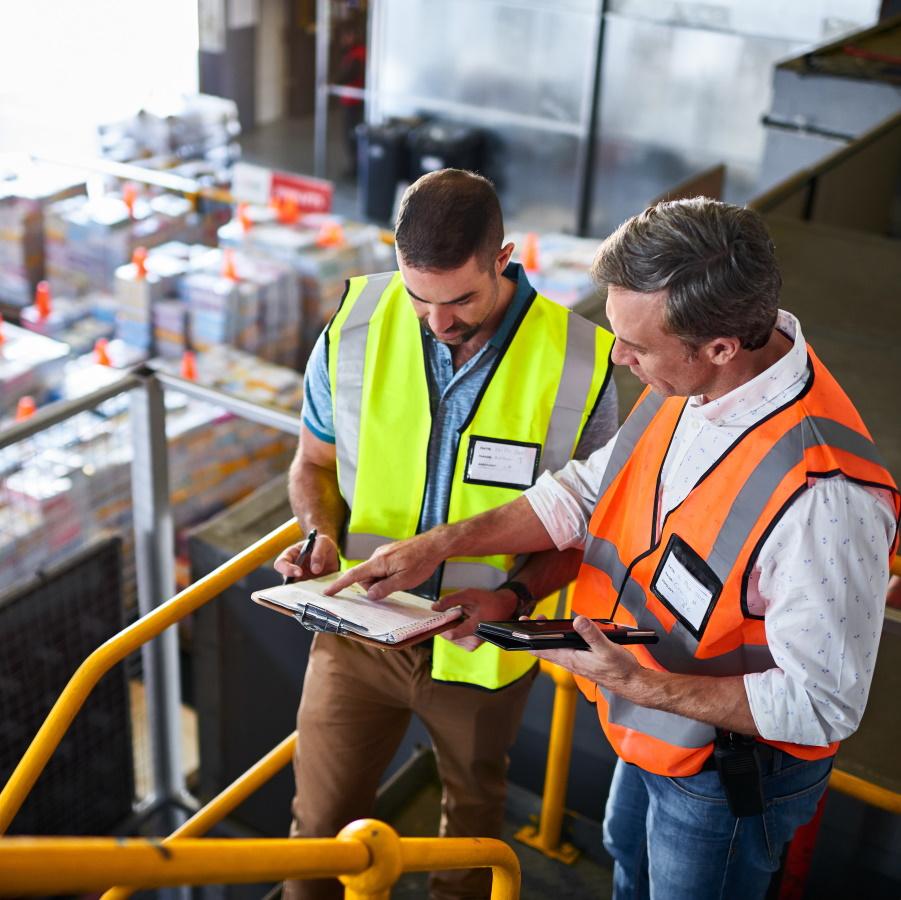 Kaksi mieshenkilöä, joilla huomioliivit päällä, varastotilan porrastasanteella tarkastelevat yhdessä paperilistaa.