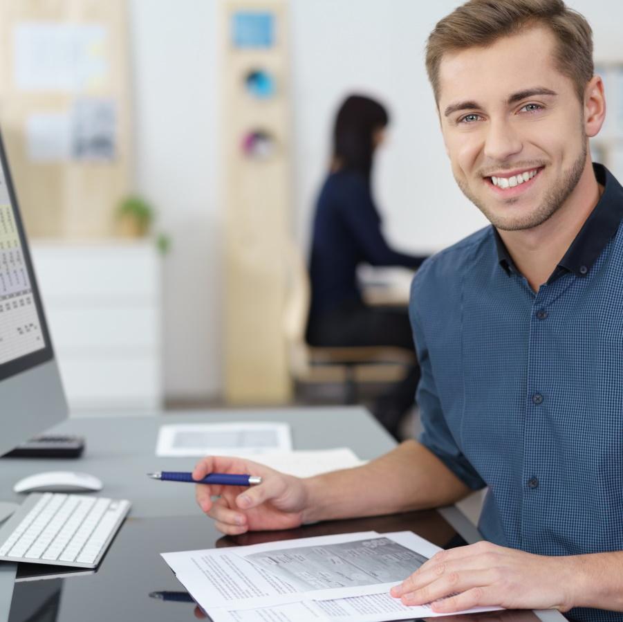Mies työpöydän ääressä, kynä kädessä. Pöydällä tietokone ja papereita. Mies katsoo kameraan.