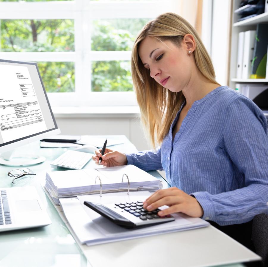 Nainen työpöydän ääressä katsoo laskinta, joka on mapin päällä. Tietokoneen ruudulla laskulomake.