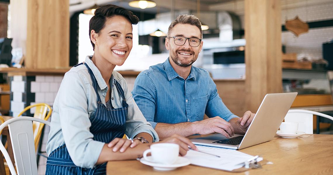 Nainen ja mies työskentelevät tietokoneen ääressä ravintolassa.