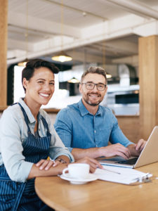 Nainen ja mies työskentelevät tietokoneen ääressä kahvilassa.