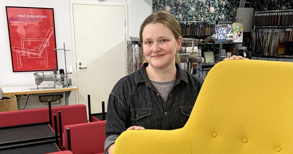 """""""Nainen hymyilee keltaisen nojatuolin takana."""""""
